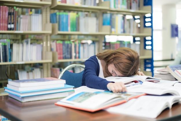 Müder asiatischer student mit vielen schlafenden büchern, während lesebuch prüfung in der bibliothek vorbereiten
