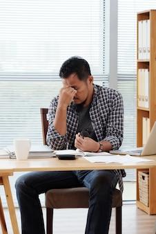 Müder asiatischer unternehmer, der bei tisch im büro sitzt und seine stirn reibt