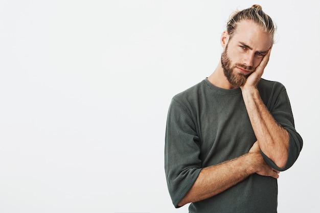 Müder attraktiver mann mit stilvoller frisur und bart im grauen hemd erschöpft aussehend
