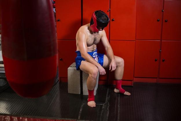 Müder boxer, der im umkleideraum sitzt