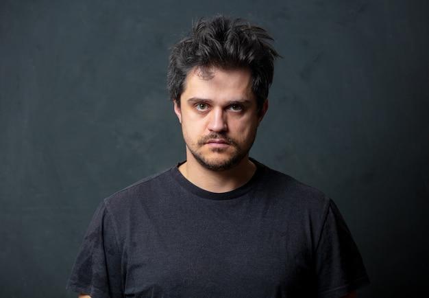 Müder brunet-mann im schwarzen t-shirt auf dunkler wand