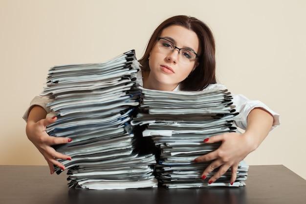 Müder buchhalter umarmt große stapel von dokumenten