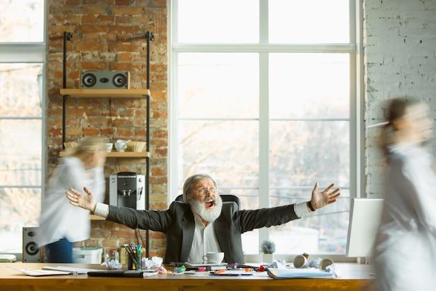 Müder chef, der an seinem arbeitsplatz ruht, während beschäftigte leute, die sich nahe bewegen, verschwommen sind. büroangestellter, manager, der arbeitet, kaffee trinkt und anweisungen für seine kollegen gibt. business-, work-, workload-konzept.