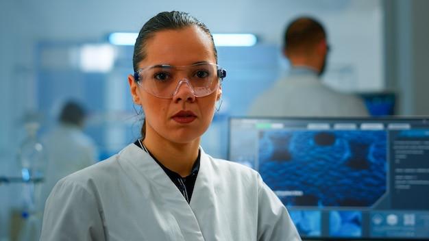 Müder chemiker, der die kamera in einem modern ausgestatteten labor seufzt. multiethnisches team, das die virusentwicklung mit hightech- und chemiewerkzeugen für wissenschaftliche forschung und impfstoffentwicklung untersucht.