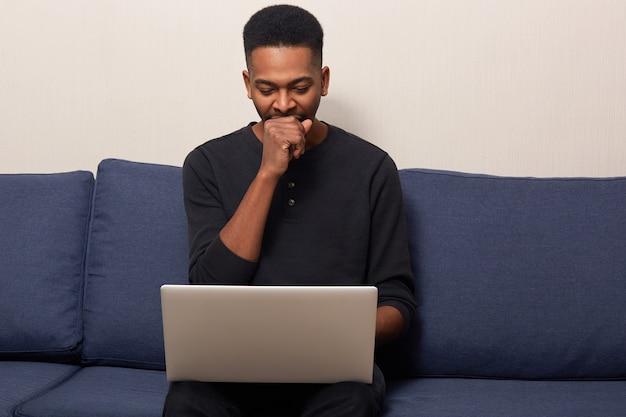 Müder, dunkelhäutiger, gutaussehender mann, der am laptop arbeitet, drahtloses internet nutzt, gähnt und erschöpft aussieht, in einen schwarzen freizeitpullover gekleidet, auf dem sofa sitzt und überarbeitet ist.