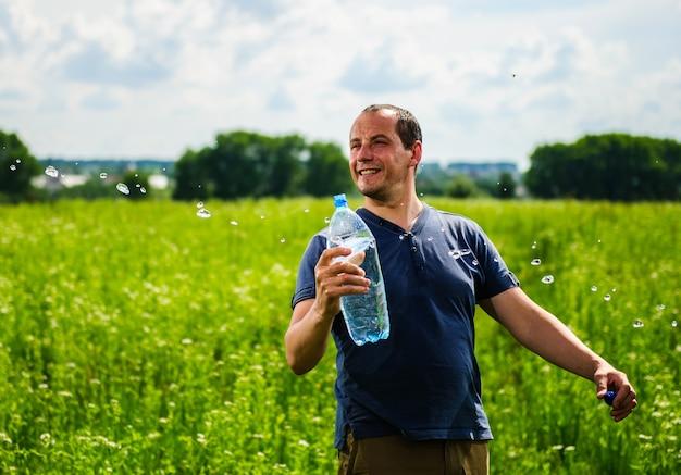 Müder durstiger bauer trinkt wasser auf dem feld während der pause von der landwirtschaftlichen tätigkeit