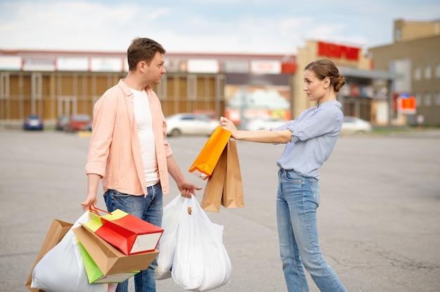 Müder ehemann, der taschen auf supermarktparkplätzen trägt. zufriedene kunden mit einkäufen in der nähe des einkaufszentrums, fahrzeuge im hintergrund, familienpaar im markt