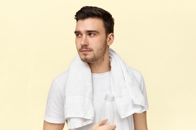 Müder, ernsthafter junger mann, der sich nach dem cardio-training ausruht und ein weißes handtuch um den hals trägt und wasser aus einer plastikflasche trinkt