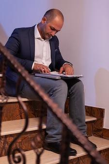 Müder, erschöpfter geschäftsmann, der überarbeitung macht, um am späten abend ein professionelles finanzprojekt vor ablauf der frist abzuschließen. unternehmer, der spät abends arbeitet, sitzt auf der treppe im gebäude aus
