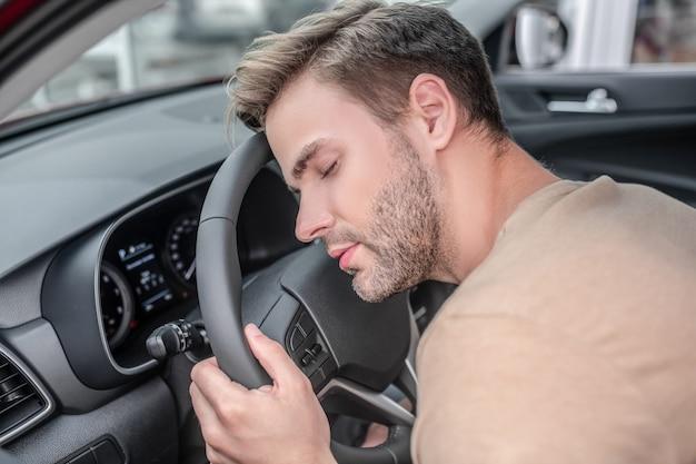 Müder fahrer. der dösende mann in hellem t-shirt mit dem kopf, der auf dem lenkrad des autos ruht, ist tagsüber müde