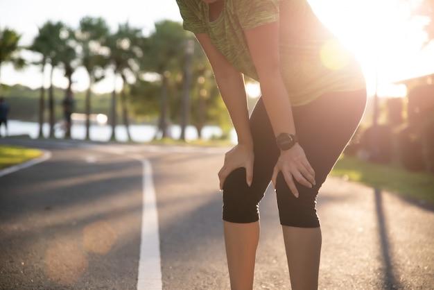 Müder frauenläufer, der eine pause nachdem dem laufen und training am sonnigen morgen macht