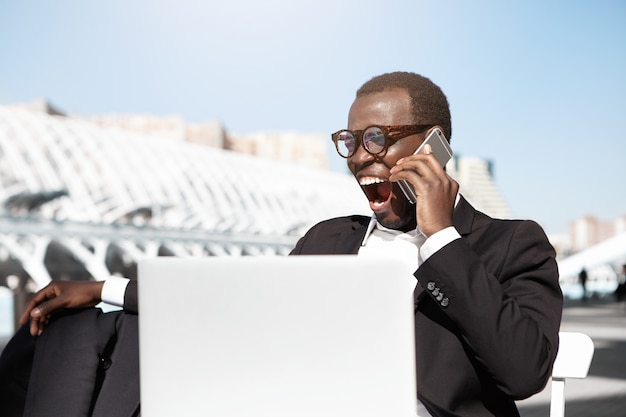 Müder gähnender junger afroamerikanischer bankier, der formell gekleidet am kaffeetisch im freien vor dem notebook sitzt und auf dem handy spricht, während er auf sein mittagessen wartet und einen schläfrigen blick langweilt
