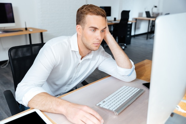 Müder, gelangweilter junger geschäftsmann, der im büro mit computer sitzt und arbeitet
