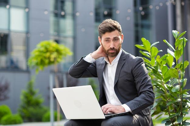 Müder geschäftsmann, der an einem öffentlichen ort auf einer laptopbank arbeitet, verärgert in depressionen, die mit dem ergebnis seiner arbeit nicht zufrieden sind