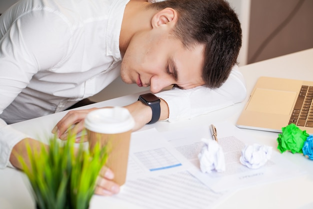 Müder geschäftsmann, der auf einem laptop im büro schläft