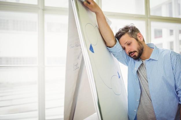 Müder geschäftsmann, der auf whiteboard im büro sich lehnt
