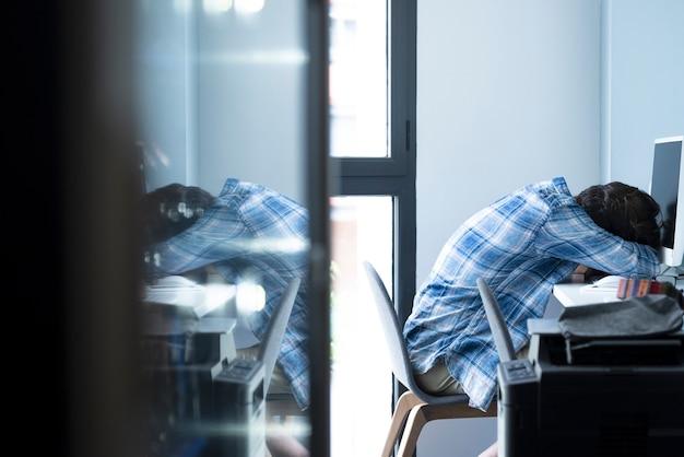 Müder geschäftsmann, der beim arbeiten am desktop-computer schläft. mann entspannt sich am arbeitsplatz mit monitor auf dem tisch. erschöpfter mann, der döst, während er vom homeoffice aus am computer arbeitet