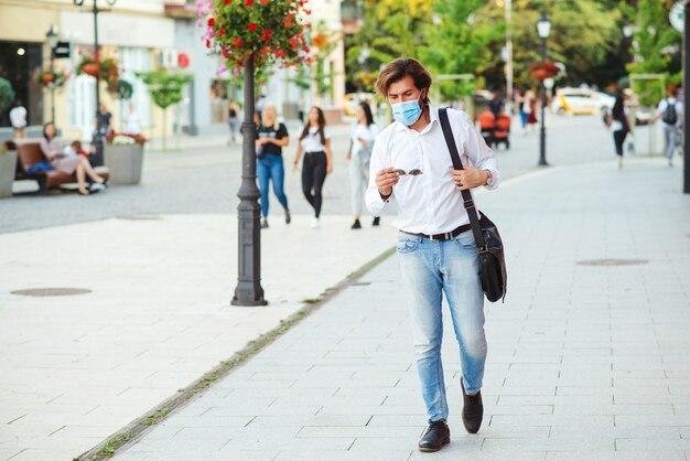 Müder geschäftsmann, der gesichtsmaske an stadtstraße trägt.