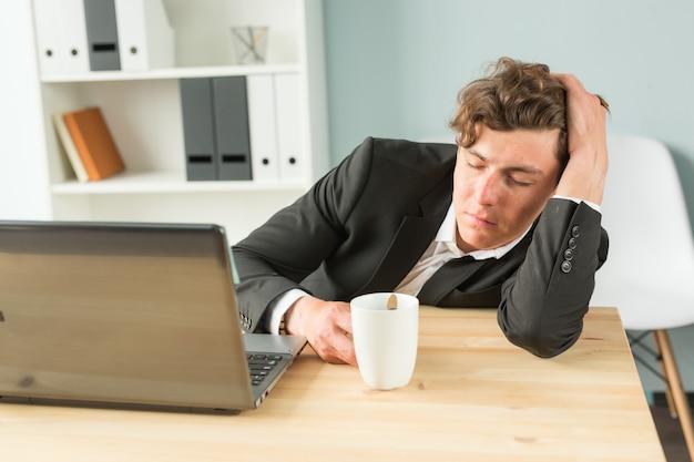 Müder geschäftsmann, der nach hartem arbeitstag in schläft