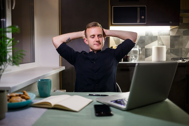 Müder geschäftsmann, der zu hause am tisch sitzt, modernes gemütliches haus, blick auf den laptop-bildschirm, freut sich mit stolz auf die geleistete arbeit, ruhige person ruht sich aus, hände ruhen hinter dem kopf