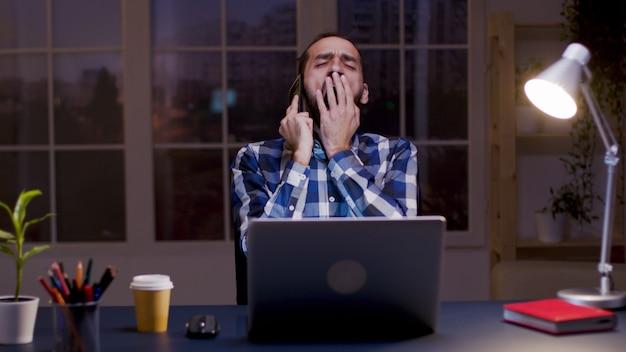 Müder geschäftsmann gähnt beim telefonieren in seinem home office. überarbeiteter geschäftsmann. spät arbeiten.