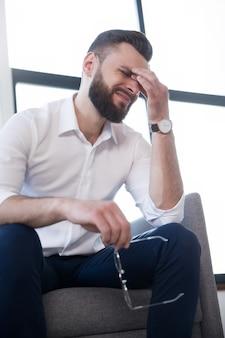 Müder geschäftsmann mit stress hat kopfschmerzen und sitzt mit schmerzen im gesicht auf der couch