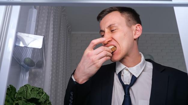 Müder geschäftsmann nimmt sandwich mit butter aus dem kühlschrank