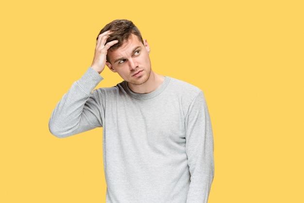 Müder geschäftsmann oder der ernste junge mann, der kamera über gelbem studio betrachtet