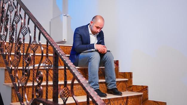 Müder gestresster geschäftsmann, der die konzentration auf die geschäftsfrist am arbeitsplatz verliert und den laptop seufzt, der im treppenhaus sitzt. unternehmensunternehmer, der überstunden im finanzgebäude macht.