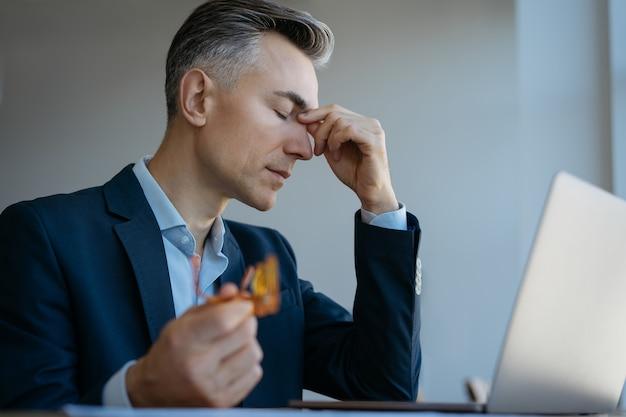 Müder gestresster geschäftsmann, der laptop hält, der brillen hält, die im büro sitzen, fehlergeschäft.