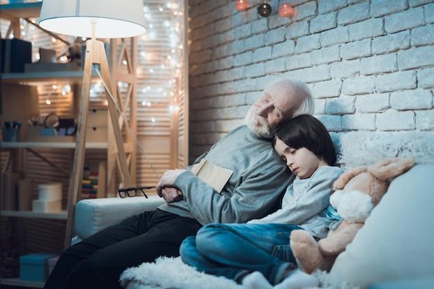 Müder großvater und granson, die nach hartem tag schläft