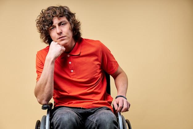 Müder invalide will sich erholen und wieder auf die beine kommen, sitzt erschöpft im rollstuhl und schaut in die kamera, stützt sich auf einen arm. isoliert