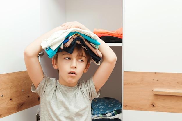 Müder junge, der einen kleiderstapel auf seinem kopf hält