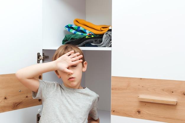 Müder junge macht ordnung in seiner garderobe zu hause. netter junge, der kleidung im schrank organisiert. bestellung im schrank. kleiderschrank mit kinderkleidung.