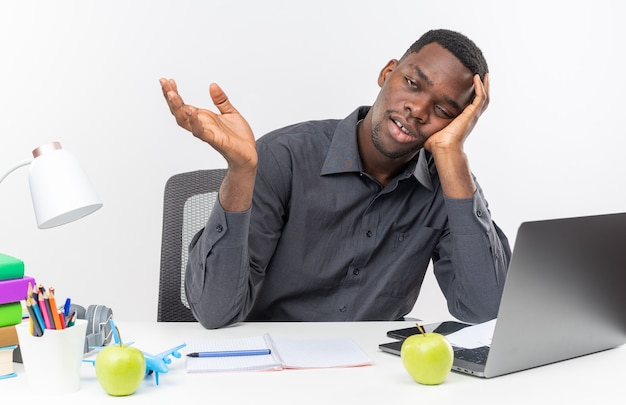 Müder junger afroamerikanischer student, der am schreibtisch mit schulwerkzeugen sitzt, den kopf auf seine hand legt und die hand offen hält