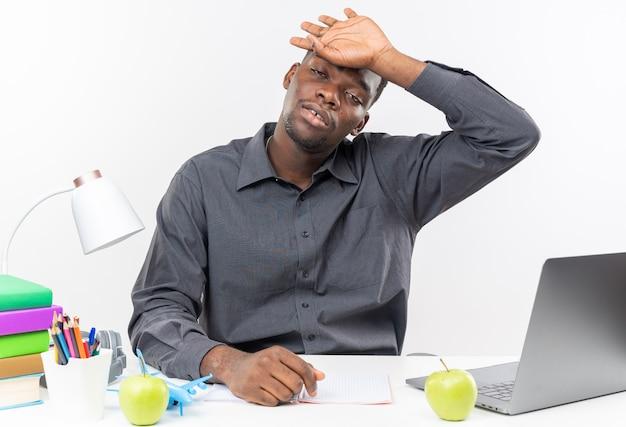 Müder junger afroamerikanischer student, der am schreibtisch mit schulwerkzeugen sitzt und die hand auf seine stirn legt, isoliert auf weißer wand