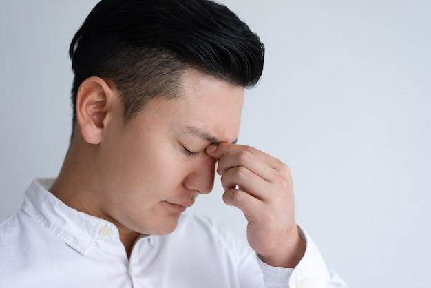 Müder junger asiatischer mann, der seine nasenbrücke berührt
