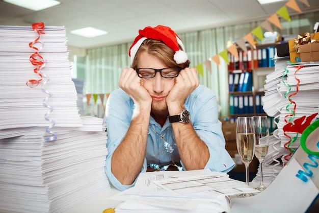 Müder junger geschäftsmann, der am arbeitsplatz unter papieren am weihnachtstag sitzt.