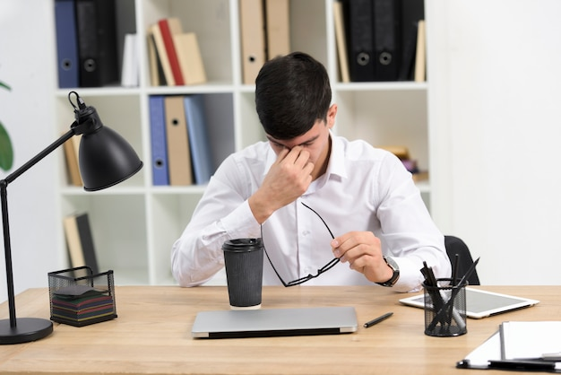 Müder junger geschäftsmann, der in der hand brillen mit mitnehmerkaffeetasse und laptop auf schreibtisch hält
