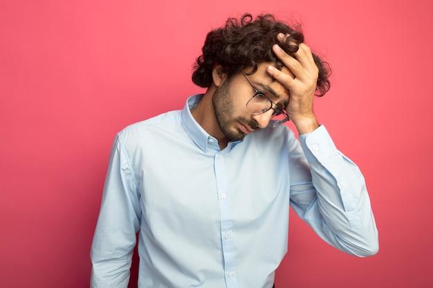 Müder junger gutaussehender mann, der eine brille trägt, die hand auf kopf setzt, der lokal auf rosa wand schaut