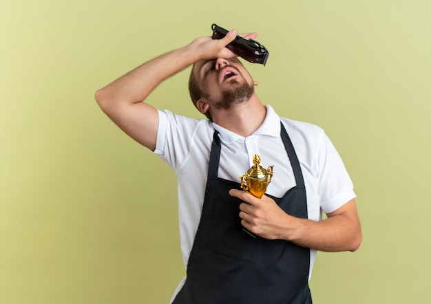 Müder junger hübscher friseur, der haarschneidemaschinen und siegerbecher hält hand auf stirn mit geschlossenen augen lokalisiert auf olivgrüner wand