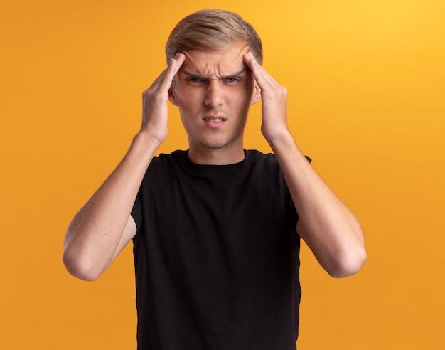 Müder junger hübscher kerl, der schwarzes hemd trägt, das hände auf stirn lokalisiert auf gelber wand setzt