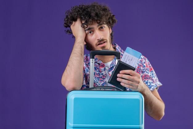 Müder junger hübscher lockiger reisender mann, der flugtickets und geldbörse mit koffer hält, der hand auf kopf auf isolierte lila wand mit kopienraum setzt