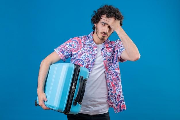 Müder junger hübscher reisender mann, der koffer mit hand auf stirn auf isolierter blauer wand mit kopienraum hält