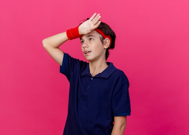 Müder junger hübscher sportlicher junge, der stirnband und armbänder mit zahnspangen trägt, die hand auf stirn halten, die lokal auf purpurrotem hintergrund mit kopienraum nach oben schaut