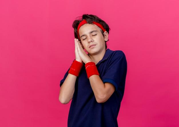 Müder junger hübscher sportlicher junge, der stirnband und armbänder mit zahnspangen trägt, die schlafgeste lokalisiert auf purpurrotem hintergrund mit kopienraum tun