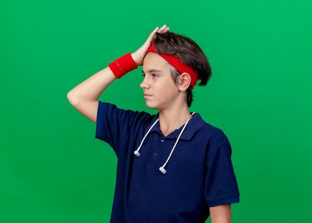 Müder junger hübscher sportlicher junge, der stirnband und armbänder und kopfhörer am hals mit zahnspangen trägt, die gerade halten hand auf kopf lokalisiert auf grünem hintergrund mit kopienraum suchen