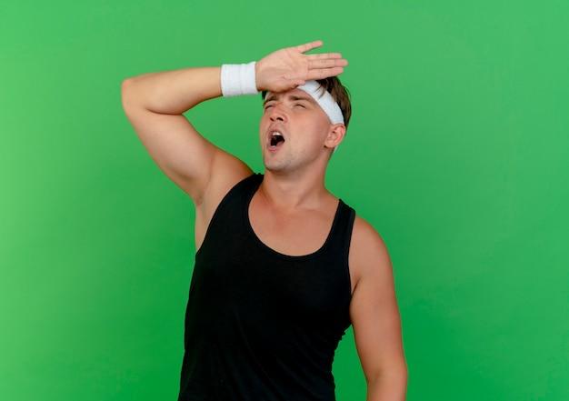Müder junger hübscher sportlicher mann, der stirnband und armbänder sucht, die hand auf stirn lokalisiert auf grünem hintergrund mit kopienraum suchen