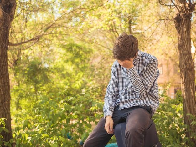 Müder junger jugendlicher, der auf der großen gepäckkoffer-tasche im freien in der sommerstadtstraße sitzt