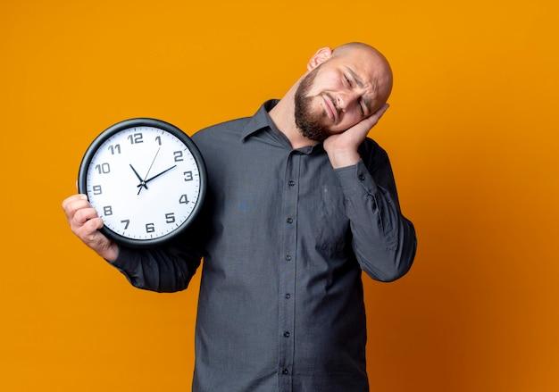 Müder junger kahlköpfiger callcenter-mann, der uhr hält und schlafgeste tut, die auf orange wand lokalisiert wird